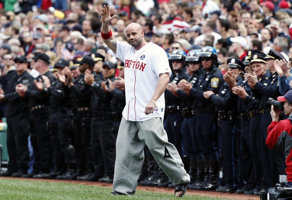 Boston Marathon bombing victim Steven Byrne waves as he comes onto the field for a ceremonial first pitch before a baseball game between the Boston Red Sox and the Kansas City Royals in Boston, Saturday, April 20, 2013. (AP Photo/Michael Dwyer)