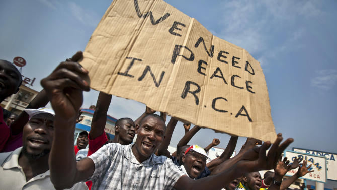 Several hundred protesting merchants, one holding a placard using the french acronym of the country's name, hold a demonstration calling for peace as negotiators prepare for talks with rebels from the north, in downtown Bangui, Central African Republic Saturday, Jan. 5, 2013. The U.N. Security Council urged rebels in the Central African Republic on Friday to halt their military offensive, withdraw from cities they have seized, and take part in negotiations to find a political solution to the impoverished country's longstanding problems. (AP Photo/Ben Curtis)