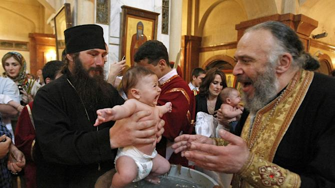 Georgian babies are baptized at the Holy Trinity Cathedral in Tbilisi, Georgia, on Sunday, May 6, 2012. Many of the parents of the 400 babies baptized on Sunday said Georgian Orthodox Church Patriarch Ilia II was instrumental in their decision to have a third or fourth child. Patriarch Ilia II  promised to become the godfather of all babies born into Orthodox Christian families who already have two or more children and since 2008 has gained nearly 11,000 godchildren. (AP Photo/ Shakh Aivazov)