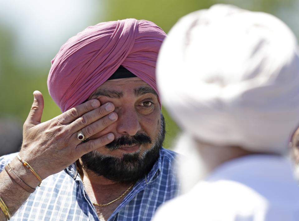A man wipes away tears outside the Sikh Temple in Oak Creek, Wis. where a shooting took place on Sunday, Aug 5, 2012. (AP Photo/Jeffrey Phelps)