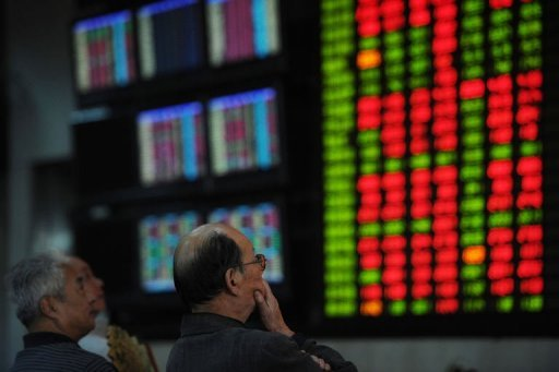 <p>Investors look at stock prices at a securities brokerage in Shanghai. Asian shares were mixed as lingering hopes for the global economy were offset by profit-taking after last week's healthy gains, while heavy losses on Wall Street added to selling pressure.</p>