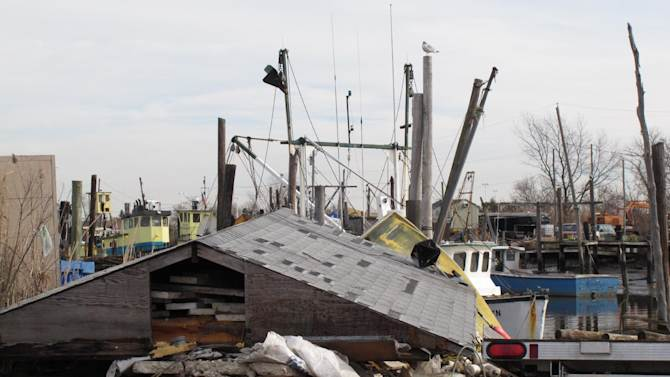 In this Dec. 12, 2012 photo, the roof of a destroyed building at the Belford fishing port in Middletown N.J., sits next to a dock. The port sustained nearly $1 million in damages, some of which its owners hope to recoup through federal storm aid. (AP Photo/Wayne Parry)