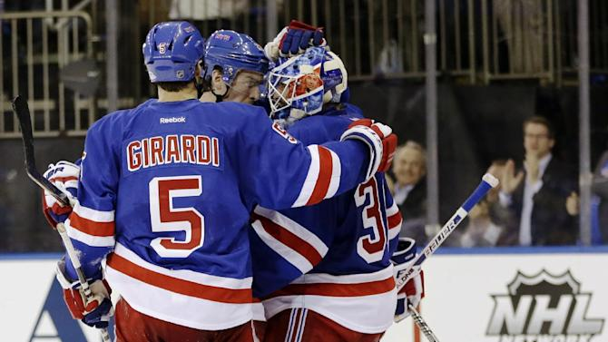 CORRECTS TO DEFENSEMAN RYAN MCDONAGH, NOT CENTER DEREK STEPAN - New York Rangers defensemen Dan Girardi (5) and Ryan McDonagh celebrate with goalie Henrik Lundqvist (30), of Sweden, after their 4-3 win over the Washington Capitals in Game 3 of their first-round NHL hockey Stanley Cup playoff series in New York, Monday, May 6, 2013. (AP Photo/Kathy Willens)