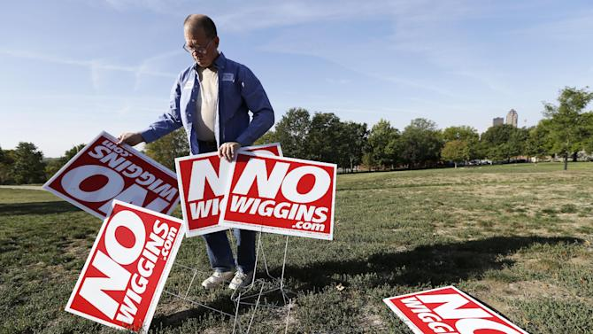 FILE - In this Sept. 24 2012, file photo Frank Ingersoll, of Des Moines, Iowa, holds yard signs before a bus tour campaign kickoff by Iowans for Freedom that is trying to convince Iowans to vote Iowa Supreme Court Justice David Wiggins off the bench in November, Monday, Sept. 24, 2012, in Des Moines, Iowa. Wiggins isn't well known outside the legal community of his state, but whether he should keep his job has become one of the most fiercely contested judicial issues on the Nov. 6 ballot because of what he symbolizes in the debate over gay marriage. (AP Photo/Charlie Neibergall, File)