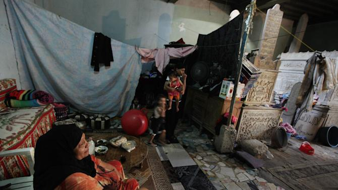 In this photo taken on Monday, May 21, 2012, an Egyptian family lives in a room that has two tombs in it in a necropolis called the City of the Dead, in Cairo, Egypt. The City of the Dead is a 4 mile (6.4 kilometer) long necropolis where thousands of Egyptians are forced to live and work alongside graves due to the scarcity of housing in the capital. (AP Photo/Khalil Hamra)