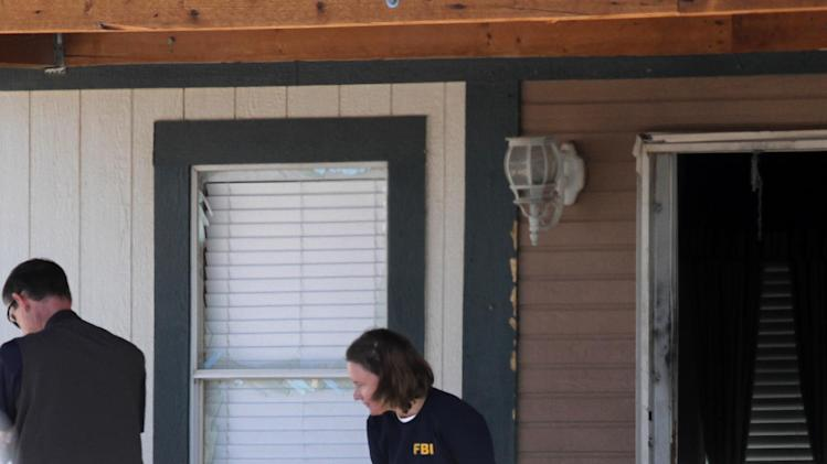 Federal agents are seen outside a house in Anthony, N.M., Wednesday, May 8, 2013. Residents of this small New Mexico border town woke Wednesday to the sounds of helicopters, bangs and screaming as federal and local agents conducted an early morning sweep on at least two homes.  (AP Photo/Juan Carlos Llorca)