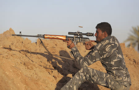 A Shi'ite fighter aims using a sniper rifle during a patrol in Jurf al-Sakhar