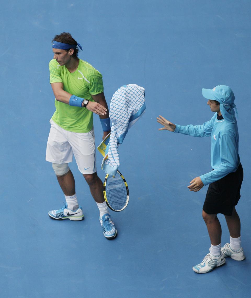 Spain's Rafael Nadal passes his towel to a ball boy during his third round match against Slovakia's Lukas Lacko at the Australian Open tennis championship, in Melbourne, Australia, Friday, Jan. 20, 2012. (AP Photo/John Donegan)