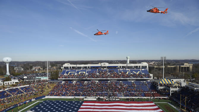 Helicopters flyover the stadium and a large American flag before the Military Bowl NCAA college football game between Virginia Tech and Cincinnati, Saturday, Dec. 27, 2014, in Annapolis, Md. (AP Photo/Nick Wass)