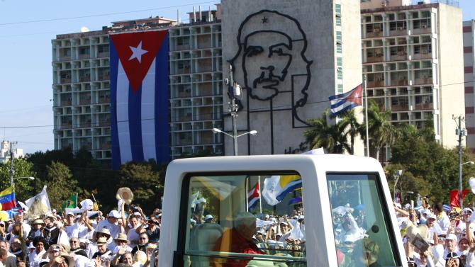 Back dropped by an image of Cuba's revolutionary hero Ernesto 'Che' Guevara, Pope Benedict XVI waves to faithful from his popemobile as arrives at Revolution Square for a Mass in Havana, Cuba, Wednesday, March. 28, 2012. (AP Photo/Ramon Espinosa)