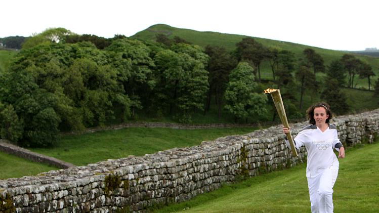 Charlotte Proud, carries the Olympic Torch at Housesteads roman fort which is along Hadrian's Wall in Housesteads, England, Saturday, June 16, 2012. The Olympic Torch is continuing its relay journey around the country, and is scheduled to arrive at the opening ceremony of the London 2012 Olympic Games. (AP Photo/Scott Heppell)
