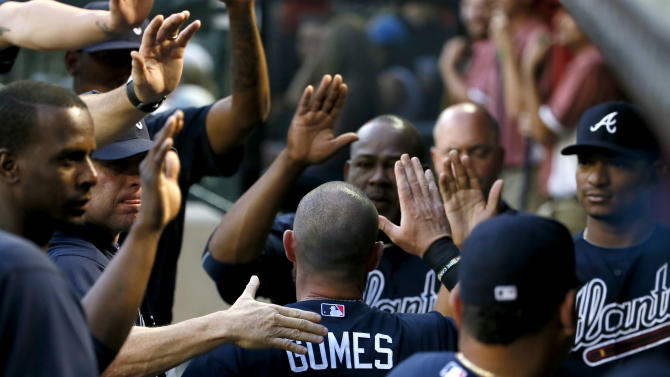Atlanta Braves' Jonny Gomes (7) is greeted in the dugout after scoring on a two-RBI double by teammate Alex Wood during the second inning of a baseball game against the Arizona Diamondbacks, Monday, June 1, 2015, in Phoenix. (AP Photo/Matt York)