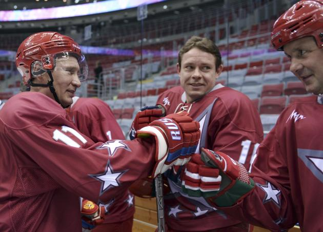 Russian President Putin speaks with former ice hockey player Pavel Bure during a friendly ice hockey match in the Bolshoi Ice Palace near Sochi
