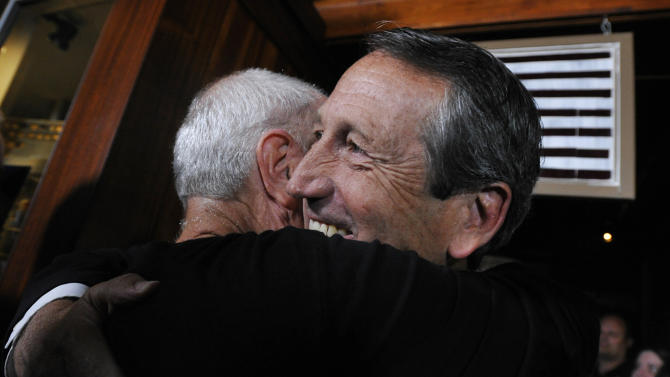 Former South Carolina Gov. Mark Sanford, right, gets a hug from a supporter before giving his victory speech on Tuesday, May 7, 2013, in Mt. Pleasant, S.C. Sanford won back his old congressional seat in the state's 1st District in a special election. (AP Photo/Rainier Ehrhardt)