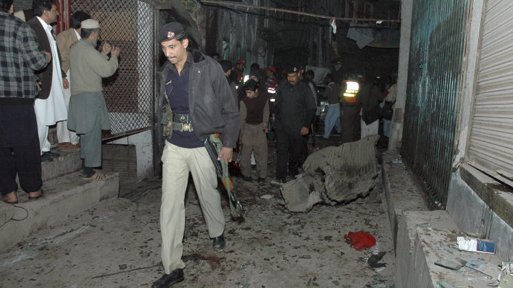 Pakistani police officers examine at the site of suicide bombing in Peshawar, Pakistan, Saturday, Dec. 22, 2012. A suicide bomber in Pakistan killed several people including a provincial government official at a political rally held Saturday by a party that has opposed the Taliban, officials said. (AP Photo/Mohammad Sajjad)