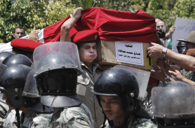 An Egyptian soldier carries the body of Tarek Mohammed, one of 16 Egyptian soldiers who were killed Sunday, Aug. 5, 2012, during an attack at a checkpoint along the Sinai border with Israel by Islamic militants with purported ties to Gaza, during the military funeral in Cairo, Egypt, Tuesday, Aug. 7, 2012. Mourners prayed for the dead at a mosque in an east Cairo suburb on Tuesday. The coffins, wrapped in Egypt&#39;s red-white-and-black flag, were later taken to a nearby square where a military ceremony is under way. Arabic on the coffin reads, &quot;Marytr Tarek Mohammed.&quot; (AP Photo/Amr Nabil)