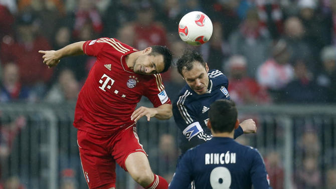 Bayern's Claudia Pizarro of Peru, left, and Hamburg's Heiko Westermann challenge for the ball during the German first division Bundesliga soccer match between FC Bayern Munich and Hamburger SV, in Munich, southern Germany, on Saturday, March 30, 2013. (AP Photo/Matthias Schrader)