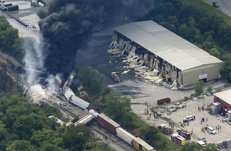 A fire burns at the site of a CSX freight train derailment, Tuesday, May 28, 2013, in Rosedale, Md., where fire officials say the train crashed into a trash truck, causing an explosion that rattled homes at least a half-mile away and collapsed nearby buildings. (AP Photo/Patrick Semansky)