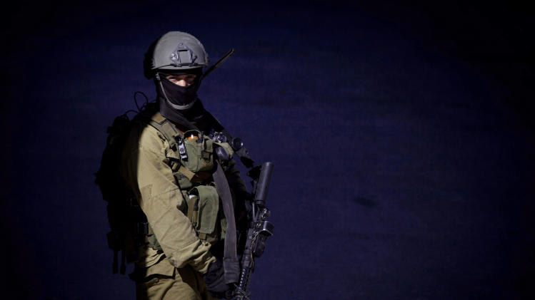 An Israeli soldier stands guard in the West Bank City of Hebron, Saturday, June 14, 2014. Israeli security forces searched the West Bank for a second day Saturday, looking for three missing teenagers, including an American, who they fear have been abducted by Palestinian militants. (AP Photo/Majdi Mohammed)