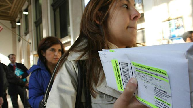 "FILE - In this April, 15, 2008, file photo, Dana Pinero, of New York, foreground, waits in line to mail tax returns for both herself and her boyfriend at the James A. Farley Main Post Office in New York. The package of tax increases and spending cuts known as the ""fiscal cliff"" takes effect on January 1, 2013, unless Congress passes a budget deal by then. The economy would be hit so hard that it would likely sink into recession in the first half of 2013, economists say. (AP Photo/Tina Fineberg, File)"