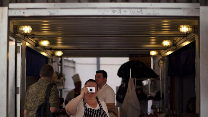 """U.S. chef Sara Jenkins, center, takes a picture before the start of dinner, in Havana, Cuba, Friday, May 11, 2012. Prominent New York City chefs are teaming up this week with culinary entrepreneurs from Havana's budding private restaurant scene, cooking up savory and sweet multi-course meals from an improvised kitchen built in a shipping container. """"Project Paladar,"""" named after Cuba's popular independent restaurants, is part of Havana's 11th Biennial, an irreverent bash attracting  artists from as many as 43 countries as well as thousands of art aficionados and collectors. (AP Photo/Ramon Espinosa)"""