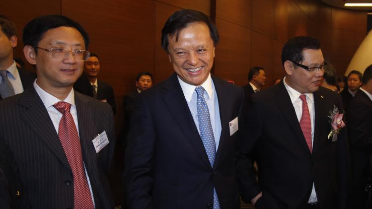 Hong Kong Exchange Chief Executive Li smiles next to Figuiniao Co Chairman Lin and Peng, branch president of Fujian branch of China Construction Bank, during the debut of six companies at the Hong Kong Stock Exchange