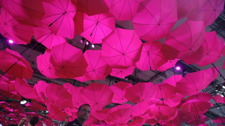 Pink umbrellas hang from the roof at the booth of German Telekom AG during the CeBit computer fair in Hanover