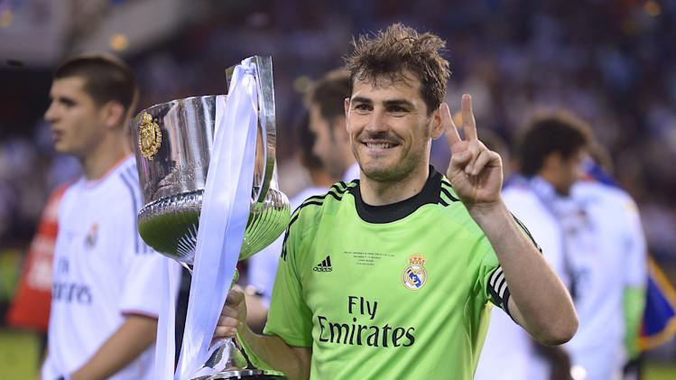 Real goalkeeper Iker Casillas poses with the trophy at the end of the final of the Copa del Rey between FC Barcelona and Real Madrid at the Mestalla stadium in Valencia, Spain, Wednesday, April 16, 2014. Real defeated Barcelona 2-1. (AP Photo/Manu Fernandez)