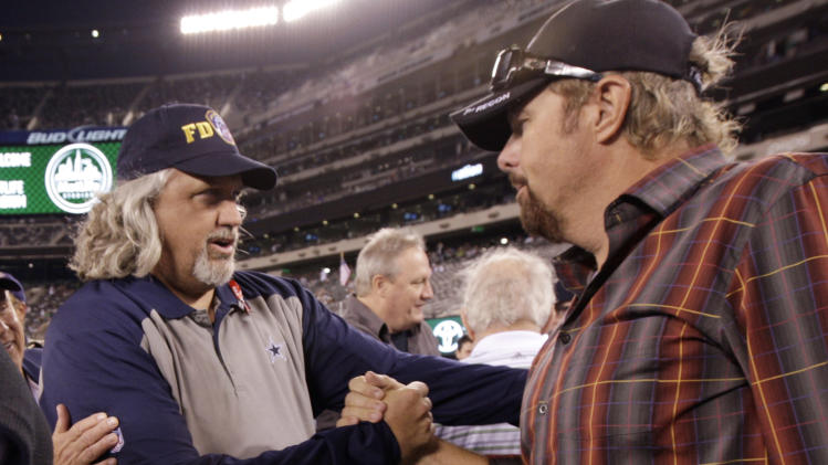 Dallas Cowboys defensive coordinator Rob Ryan, left, shakes hands with country singer Toby Keith before an NFL football game against the Dallas Cowboys Sunday, Sept. 11, 2011,  in East Rutherford, N.J. (AP Photo/Julio Cortez)