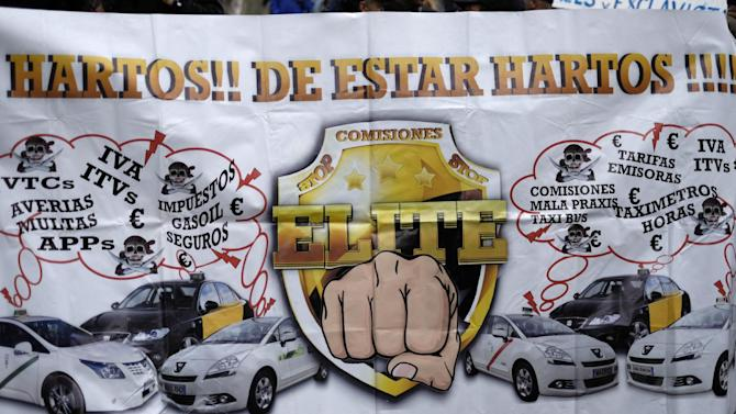 Taxi drivers hold a banner during a protest against the app Uber, in Madrid on October 14, 2014