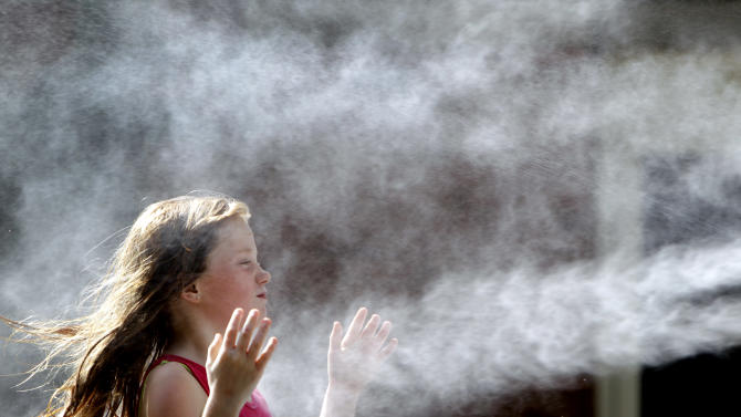 """Leena Allen, 9, cools off by standing in front of a misting fan during a visit to the Saint Louis Zoo Wednesday, July 20, 2011, in St. Louis. Much of the United States is trapped under a heat """"dome"""" caused by a huge area of high pressure that's compressing hot, moist air beneath it, leading to miserable temperatures. (AP Photo/Jeff Roberson)"""