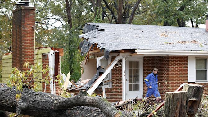 FILE - In this Tuesday, Oct. 30, 2012 file photo, a firefighter leaves the destroyed home in Pasadena, Md where Donald Cannata Sr. was killed overnight when a tree fell on it during superstorm Sandy. (AP Photo/Jose Luis Magana)