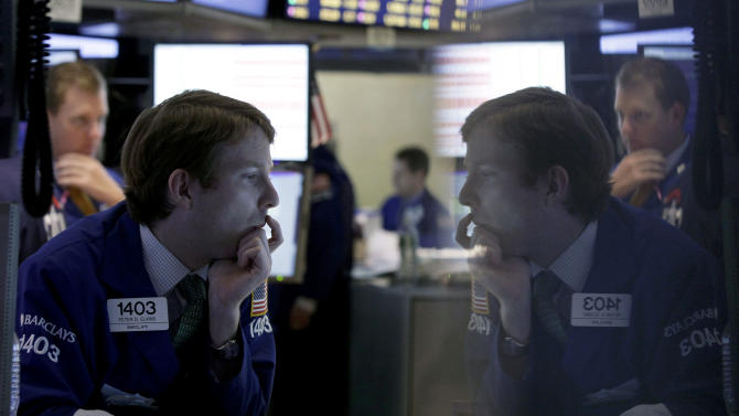 "FILE - In this Tuesday, Oct. 23, 2012 file photo, specialist Peter Elkins, foreground, is reflected in a trading post monitor as he works on the floor of the New York Stock Exchange, in New York. If Washington lawmakers can get past the ""fiscal cliff,"" many analysts say that the outlook for stocks in 2013 is good, as a recovering housing market and an improving jobs outlook helps the economy maintain a slow, but steady recovery. (AP Photo/Richard Drew, File)"