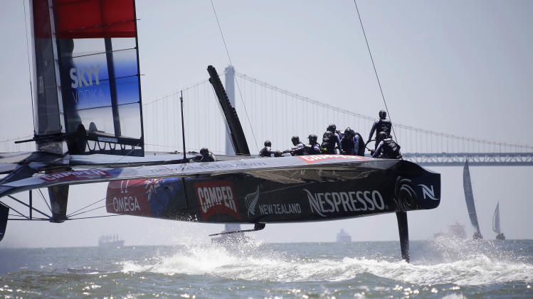 Emirates Team New Zealand train for the America's Cup with the San Francisco-Oakland Bay Bridge in the background Friday, May 24, 2013 in San Francisco. (AP Photo/Eric Risberg)
