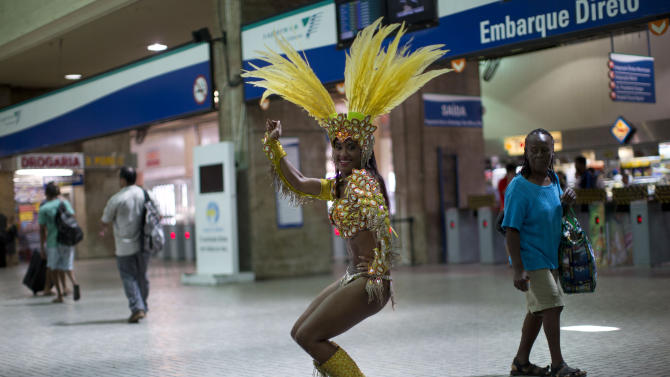 """In this photo taken Saturday, Feb. 2, 2013, samba dancer Diana Prado performs during a carnival parade at central station in Rio de Janeiro, Brazil. Prado spends her daylight hours working as a supervisor at a call center. At night, she is a samba dancer, or """"passista,"""" as they're known in Portuguese. Prado made her Carnival debut at age 19, after auditioning for a spot with the Sao Clemente, one of 13 top-tier schools that will compete for the annual titles at the Sambadrome this weekend. (AP Photo/Felipe Dana)"""