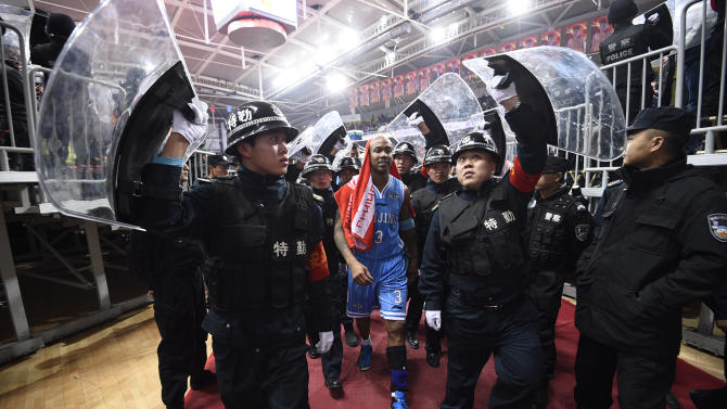 In this photo taken Sunday Nov. 30, 2014, Chinese security guards hold up shield to protect Beijing Ducks' Stephon Marbury during a CBA match between his team and Shanxi Dragons in Taiyuan in northern China's Shanxi province. After a tumultuous career in the NBA, Stephon Marbury says he's found peace in China, thriving on the court with the Beijing Ducks, mentoring young Chinese teammates and becoming one with his adopted home town. Now he has an even bigger goal in mind, to one day coach China's national team. (AP Photo) CHINA OUT