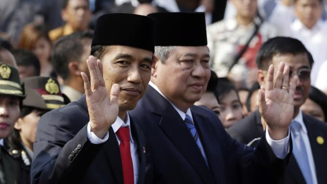 Indonesia's new President Joko Widodo waves with former  President Susilo Bambang Yudhoyono at the presidential palace in Jakarta