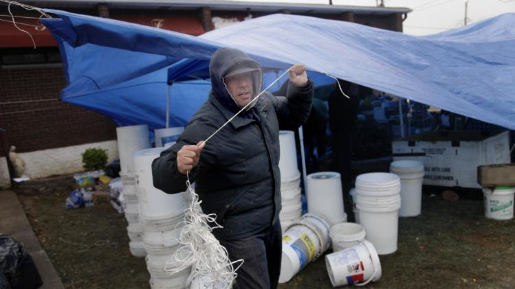Jack Biondo ties a tarp down to protect donated supplies from a coming storm in the New Dorp section of Staten Island, New York, Wednesday, Nov. 7, 2012.  Residents of New York and New Jersey who were flooded out by Superstorm Sandy are waiting with dread Wednesday for the second time in two weeks as another, weaker storm heads toward them and threatens to inundate their homes again or simply leave them shivering in the dark for even longer. (AP Photo/Seth Wenig)