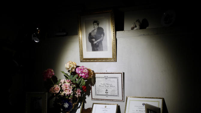 "In this Nov. 26, 2012 photo, a 1940's portrait of journalist and radio host Maria Julia Venegas, university titles and certificates are on display at her home in Lima, Peru. Venegas who began broadcasting ""Radio Club Infantil,"" a show for Peru's children in the golden age of radio and World War II, has earned a citation from Guinness World Records as the globe's longest-running radio personality. (AP Photo/Karel Navarro)"