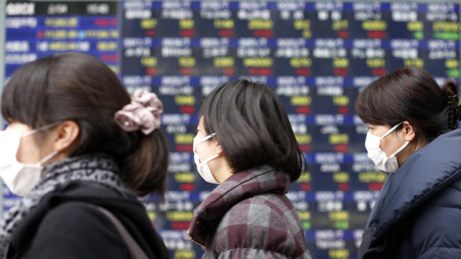 People walk by an electric stock price display of a securities firm in Tokyo Monday, Feb. 4, 2013. Asian stock markets were mostly higher Monday as investors continued to feel confident about stocks following last week's U.S. jobs report and Wall Street's rally.  (AP Photo/Koji Sasahara)
