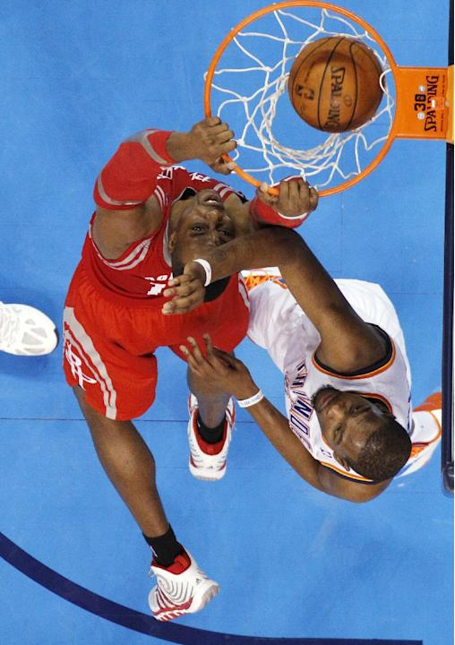 Houston Rockets center Dwight Howard, left, dunks in front of Oklahoma City Thunder forward Kevin Durant during the third quarter of an NBA basketball game in Oklahoma City, Tuesday, March 11, 2014. O