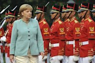 German Chancellor Angela Merkel reviews a military honor guard during a ceremony at the presidential palace in Jakarta on July 10. Merkel on Wednesday said Europe must step up its efforts to establish a free trade pact with booming Southeast Asia