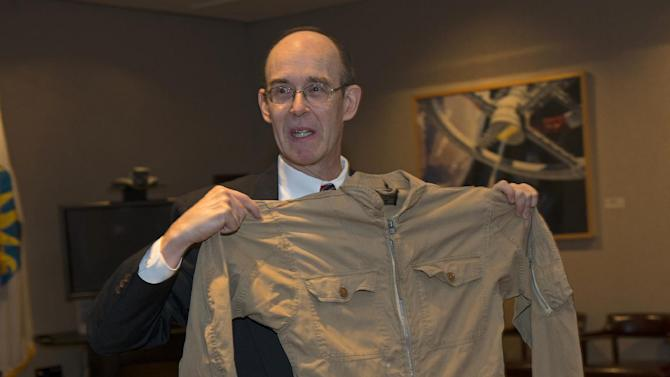 This handout photo provided by Smithsonian's National Air and Space Museum, shows David Ecker holding a flight suit worn by his father, Commander William Ecker, who flew missions over Cuba, Tuesday, Oct. 23, 2012, at the museum in Washington. The suit worn by Commander Ecker who flew a reconnaissance mission over Cuba in 1962 that photographed nuclear missile sites under construction by the onetime Soviet Union, was donated Tuesday to the Smithsonian's National Air and Space Museum. (AP Photo/Mark Avino, Smithsonian's Air and Space Museum)