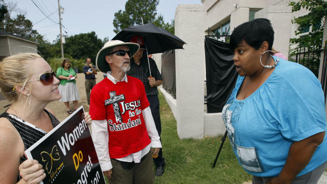 FILE- In this Monday, July 2, 2012, file photo, abortion opponents Ron Nederhoed, center, and Ashley Sigrest, left, argue with Jackson Women's Health Organization's administrator Shannon Brewer, right, over the opponent's trespassing onto the property of Mississippi's only abortion clinic in Jackson, Miss. A federal judge on Friday July 13, 2012 allowed Mississippi's anti-abortion law to take effect but said the state's only clinic can remain open and will not face any penalties as it tries to comply with new requirements. (AP Photo/Rogelio V. Solis, File)