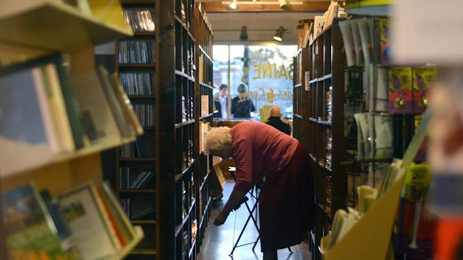 "In this Thursday, Nov. 8, 2012 photo, Rachel Lambert of Appomattox, Va., uses a flashlight to look through books at Baine's Books in Appomattox, Va. Lambert describes herself as a ""values voter"" who voted for Mitt Romney. (AP Photo/Pat Jarrett)"