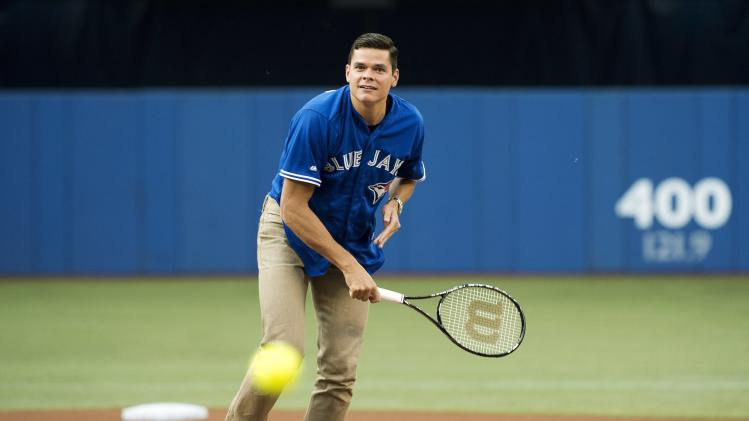 Canadian tennis star Milos Raonic serves up the ball on the pitchers mound before the Toronto Blue Jays take on the Boston Red Sox before the first inning of a baseball game, Tuesday, July 22, 2014 in Toronto. (AP Photo/The Canadian Press, Nathan Denette)
