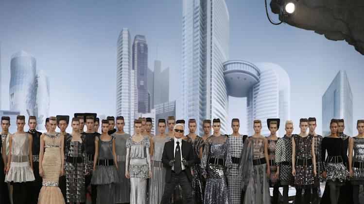 German fashion designer Karl Lagerfeld, foreground centre, surrounded by models, acknowledges applause following the presentation of the Haute Couture Fall-Winter 2013-2014 collection he designed for Chanel, Tuesday, July 2, 2013 in Paris. (AP Photo/Francois Mori)