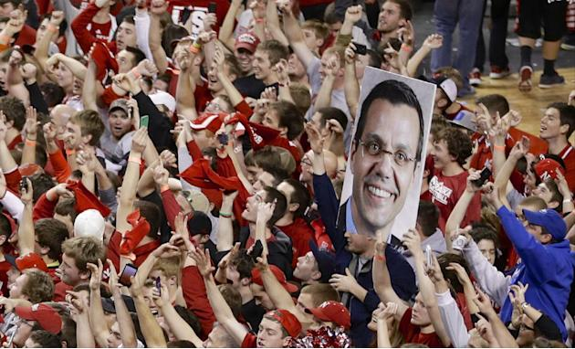 Celebrating Nebraska fans carry a sign of Nebraska coach Tim Miles as they fill the court following an NCAA college basketball game in Lincoln, Neb., Sunday, March 9, 2014. Nebraska won 77-68
