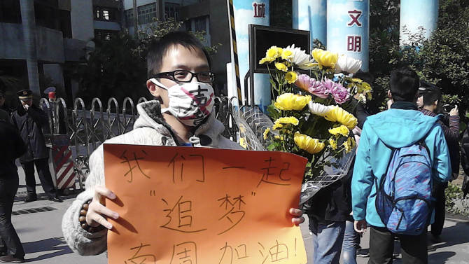 """In this photo taken and provided by activist Wu Wei, a man wearing a mask with words """"Silent"""" holds a banner reading: """"Let's chase our dreams together, go Southern Weekly newspaper"""" during a protest outside the headquarters of the newspaper in Guangzhou, Guangdong province Monday, Jan. 7, 2013. A dispute over censorship at the Chinese newspaper known for edgy reporting has prompted a few hundred people to gather in a rare street protest urging Communist Party leaders to allow greater political freedom. (AP Photo/Wu Wei) EDITORIAL USE ONLY"""