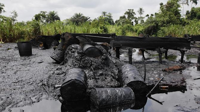 FILE- In this Saturday, May 18, 2013 file photo, an abandoned illegal refinery is seen after it was raided by Nigeria Navy at the creeks of Bayelsa, Nigeria. The Nigerian Navy says it destroyed 260 illegal oil refineries and burned 100,000 tons of contraband fuel to try to halt oil thefts bedeviling the economy of Africa's biggest petroleum producer. Commanding officer Capt. Musa Gemu said Saturday night sailors of the NNS Delta destroyed the refineries in the Warri South-West area of southern Delta region Friday night and arrested five suspects. (AP Photo/Sunday Alamba, File)